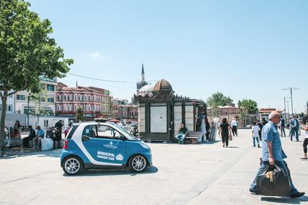 municipal editorial: Istanbul, June 15 2017: Municipal tourist team. Blue Smart car and people at Eminonu square in the middle of the day.