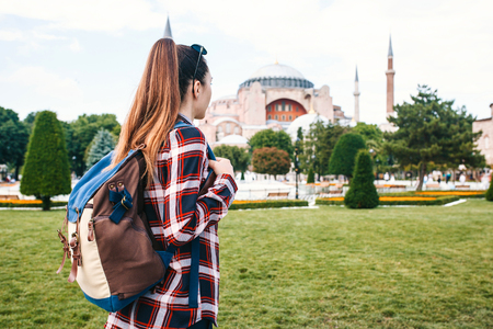 A young traveler girl with a backpack in Sultanahmet Square next to the famous Aya Sofia mosque in Istanbul in Turkey.Travel, tourism, sightseeing.
