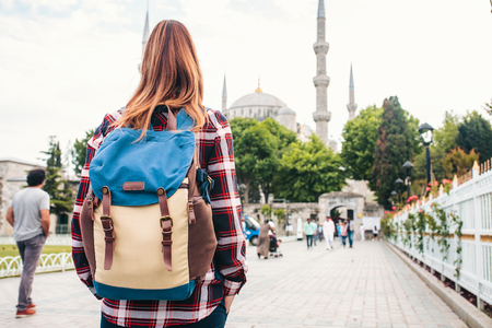 Young beautiful girl traveler with a backpack looking at a blue mosque - a famous tourist attraction of Istanbul. Travel, tourism, sightseeing. Stock Photo