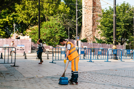 groundskeeper: Istanbul, June 15, 2017: janitor in bright orange uniform sweeping the tile on the street in Sultanahmet district.