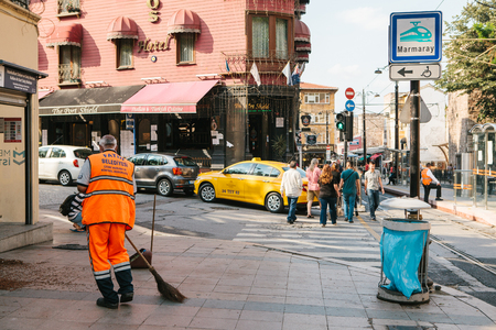 groundskeeper: Istanbul, June 15, 2017: janitor in bright orange uniform sweeping the tile on the street in Sultanahmet district