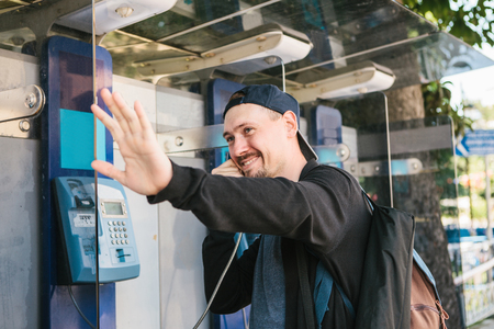 payphone: A young attractive modern man speaks at a payphone and welcomes with his hand. Communication concept.