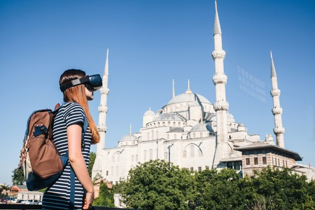 A traveler with virtual reality glasses. The concept of virtual travel around the world. In the background the blue mosque Sultanahmet in Istanbul in Turkey. Future technology concept.