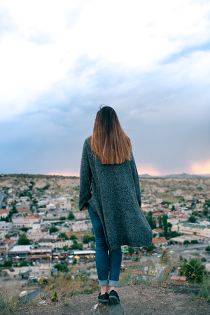 fantasize: Young woman tourist from a high point looking at the sunset over the city of Goreme in Cappadocia in Turkey and dreaming. Tourism, vacations, rest. Stock Photo