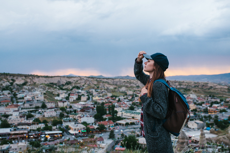 stands: Young woman tourist stands on a sunset background over the city of Goreme in Turkey. Cappadocia. Tourism, rest, vacation.
