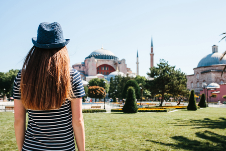A young girl traveler in a hat from the back in Sultanahmet Square next to the famous Aya Sofia mosque in Istanbul, Turkey. Travel, tourism, sightseeing.