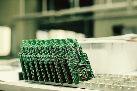 Computer boards stand in a row at the factory for the production of spare parts. Modern technologies. Foto de archivo