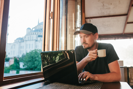 marketing online: A young male tourist blogger freelancer working on a laptop in a cafe in Istanbul. A view from the window to the world-famous Blue Mosque also called Sultanahmet.