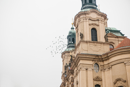 Exterior of the Church of St. Nicholas in the Old Town Square in Prague, Czech Republic. Architecture. Religious building. Birds fly near the building.