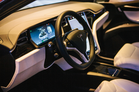 Interior of an electric car Tesla model X. Rudder with the brand name Tesla.