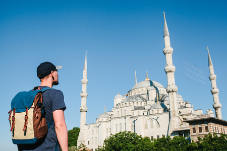 A man in a baseball cap with a backpack next to the blue mosque is a famous sight in Istanbul. Travel, tourism, sightseeing.