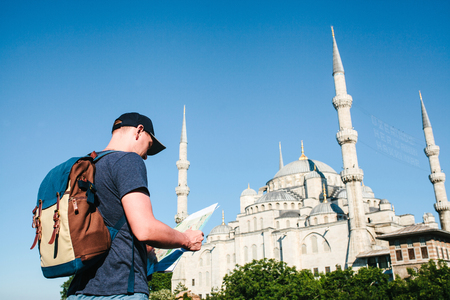 A traveler in a baseball cap with a backpack is looking at the map next to the blue mosque - the famous sight of Istanbul. Travel, tourism, sightseeing.