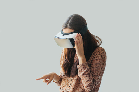 Young woman with virtual reality glasses. Modern technologies. The concept of future technology. The concept of a remote study. Stock Photo