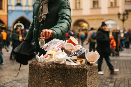 Hand of an unknown man throws disposable cup into overcrowded trash basket on the street of Prague against blurred crowd of people