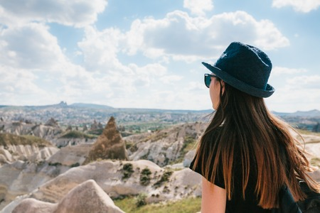 Young beautiful travel girl with a backpack on top of a hill in Cappadocia, Turkey. Travel, success, freedom, achievement.
