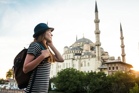 Viajero joven hermoso de la muchacha en un sombrero con una mochila que habla en un teléfono móvil cerca de la mezquita azul - la atracción turística famosa de Estambul. Viajes, turismo, excursiones.