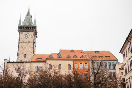 Prague, December 13, 2016: Beautiful historic buildings with red tiles on the roof and the clock tower on square in Prague standing tightly to each other