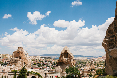 Beautiful scenery of Goreme in Cappadocia in Turkey, small houses in the midst of bizarre rocks on sunny warm day with white cumulus clouds