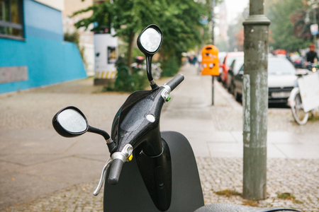 motobike: The steering wheel of an electric scooter is in the foreground, in the background is an urban view of Berlin street.