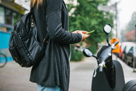 motobike: A tourist with a backpack is going to use an electric scooter through a mobile application in the phone and distally activate it. A popular vehicle in Berlin and Paris.