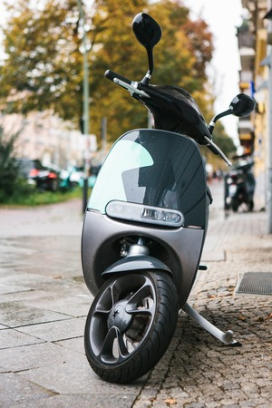 A popular vehicle in the city is called an electric scooter. In the background a street in Berlin. Stock Photo