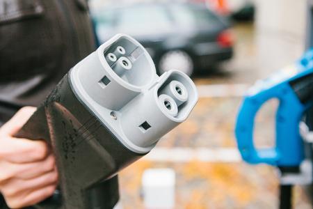 O motorista pega um cabo para carregar o veículo elétrico. Um meio de transporte moderno e ecológico que se espalhou pelo mundo. Foto de archivo - 88610925