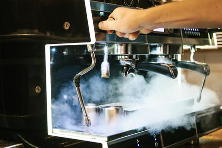 Een man herstelt een gebroken koffiezetapparaat in een café. Er is stoom, verkeerd werk. Ondersteuning en reparatie.