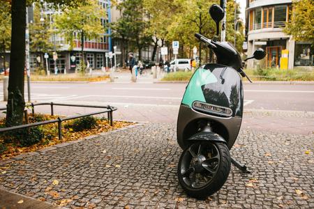Een populair voertuig in de stad wordt een elektrische scooter genoemd. Op de achtergrond een straat in Berlijn. Stockfoto