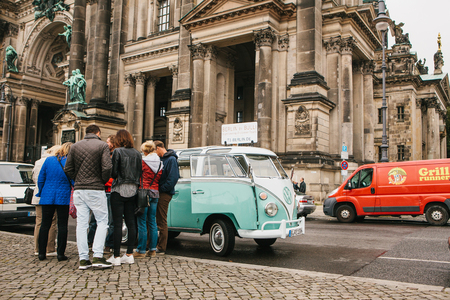 Berlin, October 1, 2017: Group of young unknown tourists book tourist trip on blue retro mini bus next to the Berlin Cathedral called Berliner Dom Editorial
