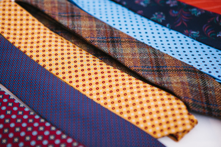 Many multi-colored ties in a row. Supplement to mens clothing in business style. Fashionable mens accessory.