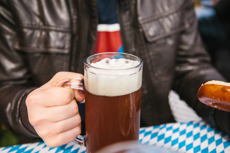 Celebrating the traditional German beer festival called Oktoberfest. A man is sitting at a table and holding a mug of beer.