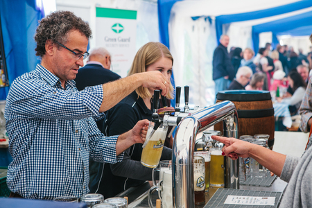 Prague, September 23, 2017: Celebrating the traditional German beer festival called Oktoberfest in the Czech Republic. The barman pours fresh beer to the visitors. The buyer shows what he needs. Editorial