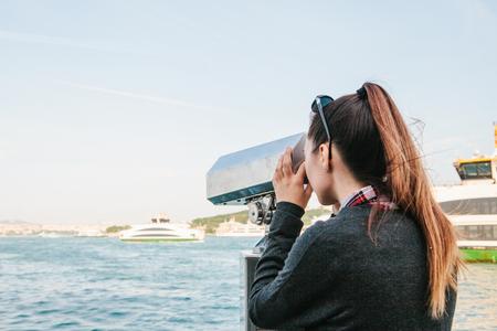 Girl looking at the sea through tourist telescope. View of the Bosphorus in Istanbul, Turkey. Standard-Bild