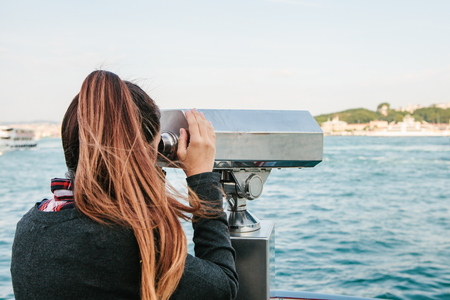 Girl looking at the sea through tourist telescope. View of the Bosphorus in Istanbul, Turkey. Stock Photo