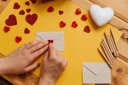 The girl wrote a letter with congratulations and pastes the envelope with a symbol in the form of a heart. Nearby lie various objects symbolizing the event. Imagens - 93965762