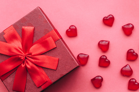 Red beautiful box with ribbon and bow on red background. Nearby are symbols in the form of a heart.