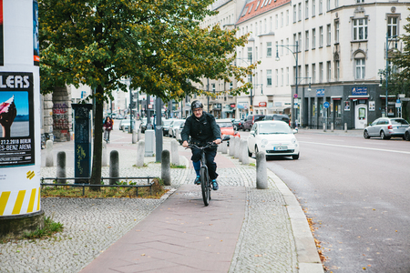 Berlin, December 12, 2017: An elderly man on a scooter rides a special bike path along the city street next to the buildings, road, cars. Eco-friendly means of transportation around the city.