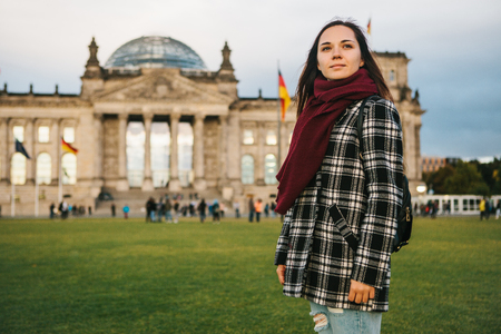 A tourist girl with a backpack next to the building called the Reichstag in Berlin in Germany. Sightseeing, tourism, travel around Europe