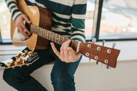 Learning to play the guitar. Music education and extracurricular lessons. Hobbies and enthusiasm for playing guitar and singing songs. To have fun. Stock Photo