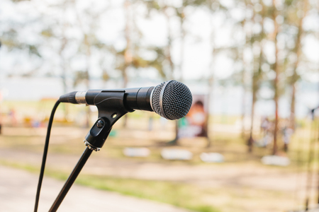 A microphone on stage. The concept of a concert in the open air. Stock Photo
