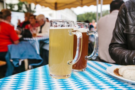 Two mugs with a light and dark beer stand on the table. Celebrating the traditional German beer festival called Oktoberfest Stock Photo