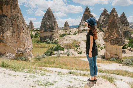 The woman stands next to the beautiful rocks and admires the landscape in Cappadocia in Turkey. She points to one of the most interesting hills. The landscape of Cappadocia.
