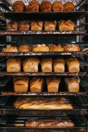 A lot of ready-made fresh bread in a bakery oven in a bakery. Bread making business. Foto de archivo