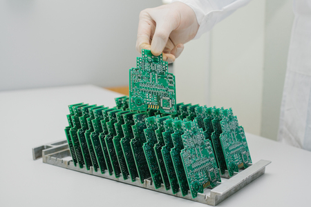 The technician takes a computer board with chips. Spare parts and components for computer equipment. Production of electronics and maintenance. The concept of high technology. Stock Photo