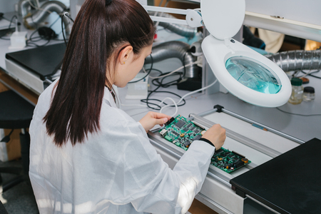 Beautiful female computer expert professional technician examining board computer in a laboratory in a factory. Technical support.