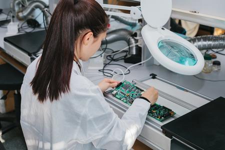 Mooie vrouwelijke computer deskundige professionele technicus die raadscomputer in een laboratorium in een fabriek onderzoeken. Technische ondersteuning.