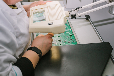Female computer expert professional technician examining board computer in a laboratory in a factory.