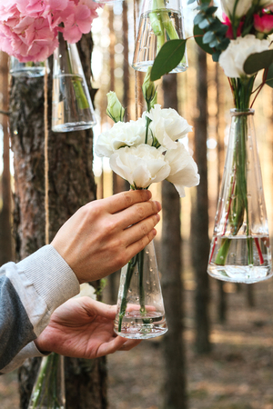 The decorator is working. Wedding flowers decoration arch in the forest. The idea of a wedding flower decoration.