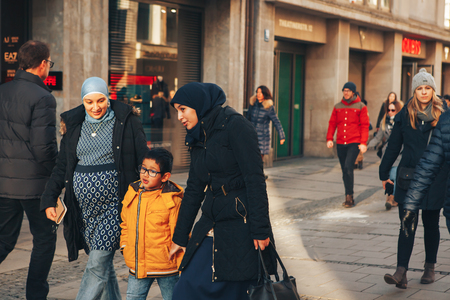 Munich, Germany, December 29, 2016: A friendly family of migrants walks down the street in Munich. Tolerance, friendliness. Everyday life in Europe.