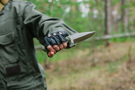 Hand of a female soldier with a knife in the woods